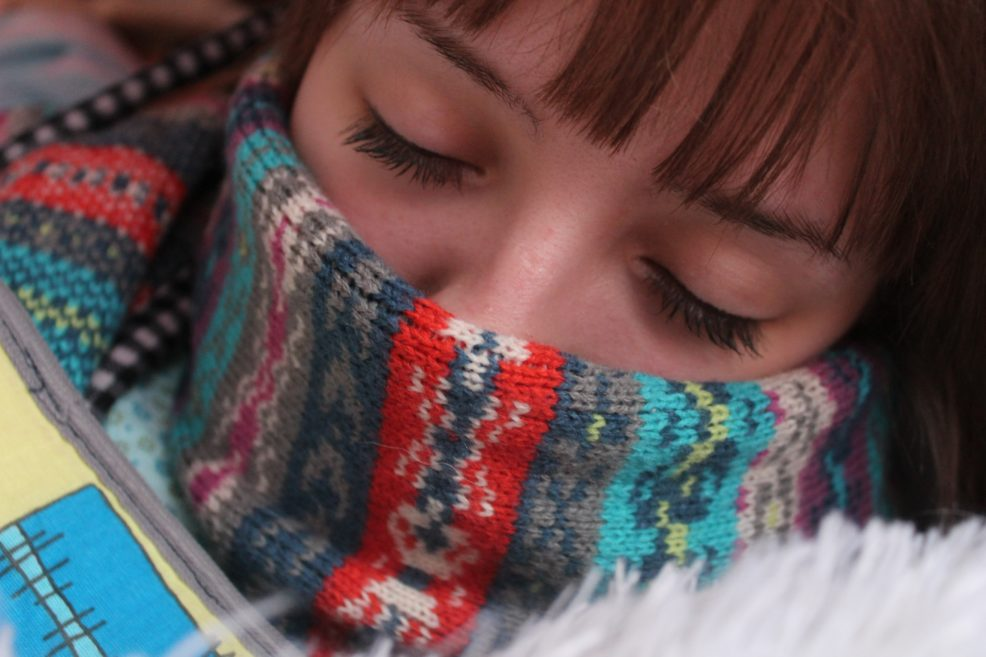 Sick woman with scarf over nose during cold and flu season