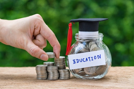 coins stacked in jar with graduation hat, funding education